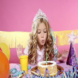 ילדה מכבה נר על עוגת יומולדת